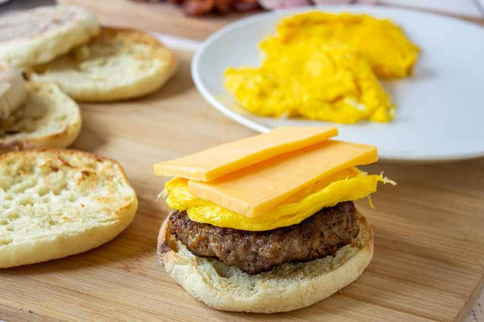An English muffin sandwich topped with sausage and slices of cheese.
