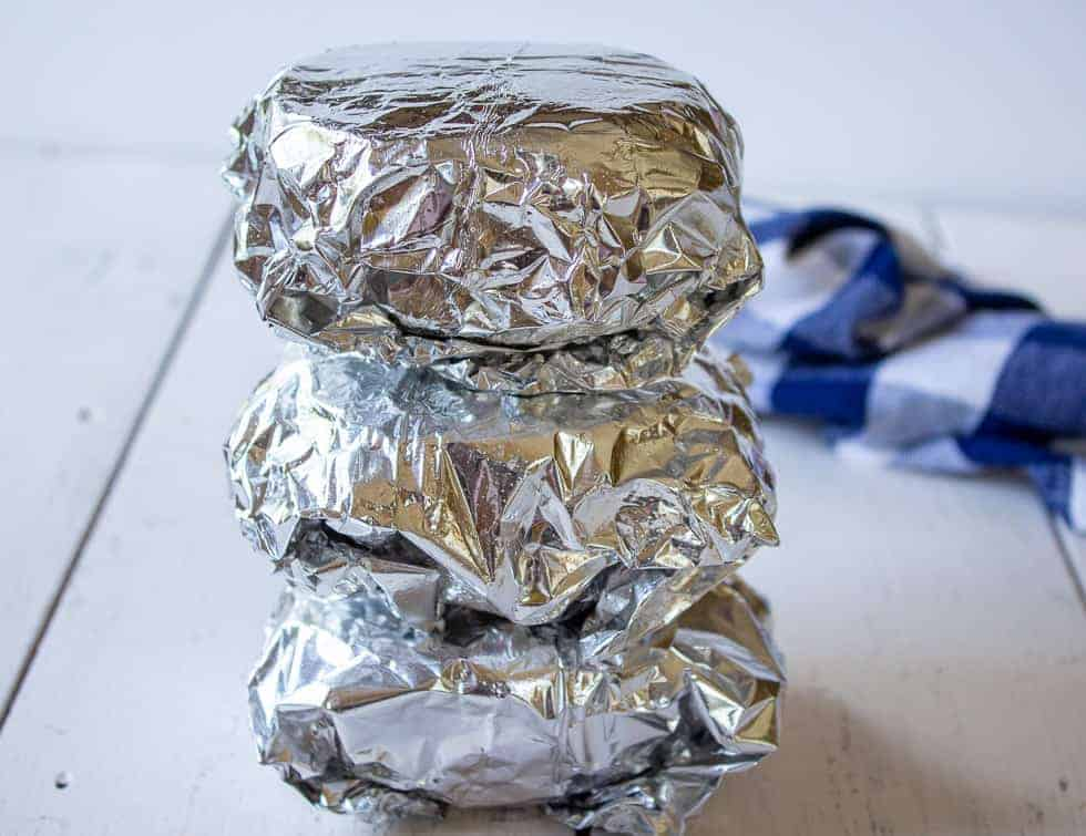 Sandwiches wrapped in foil and stacked on top of each other.