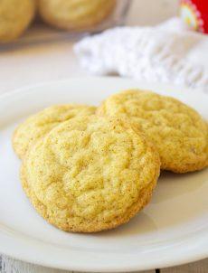 Three sugar cookies arranged on a white plate.