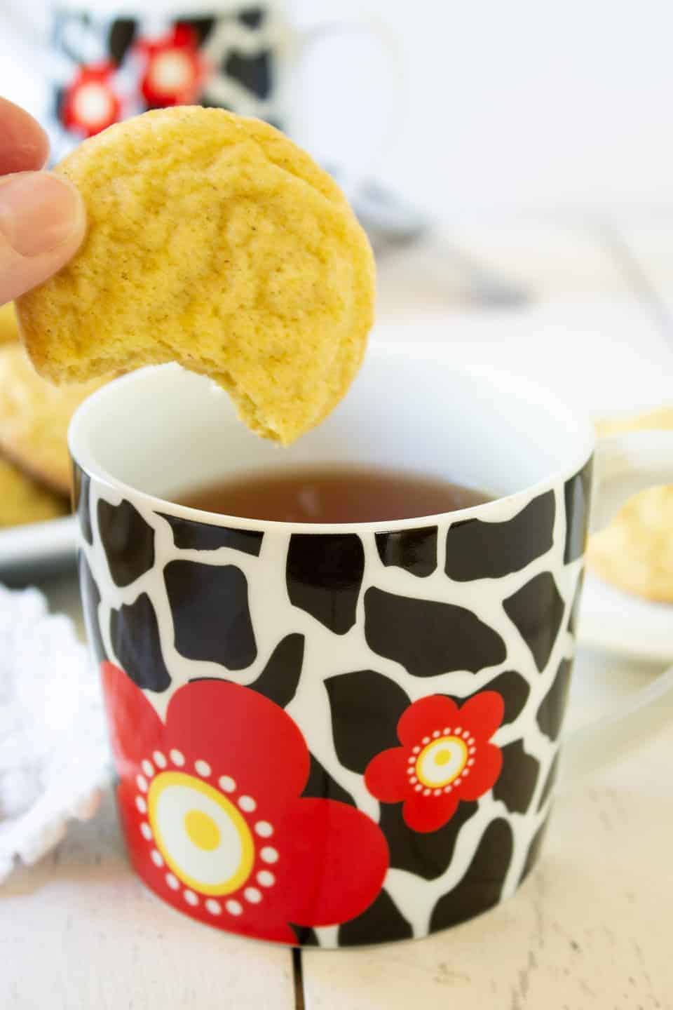 A cookie with a bite out of it being dipped into a cup of tea.