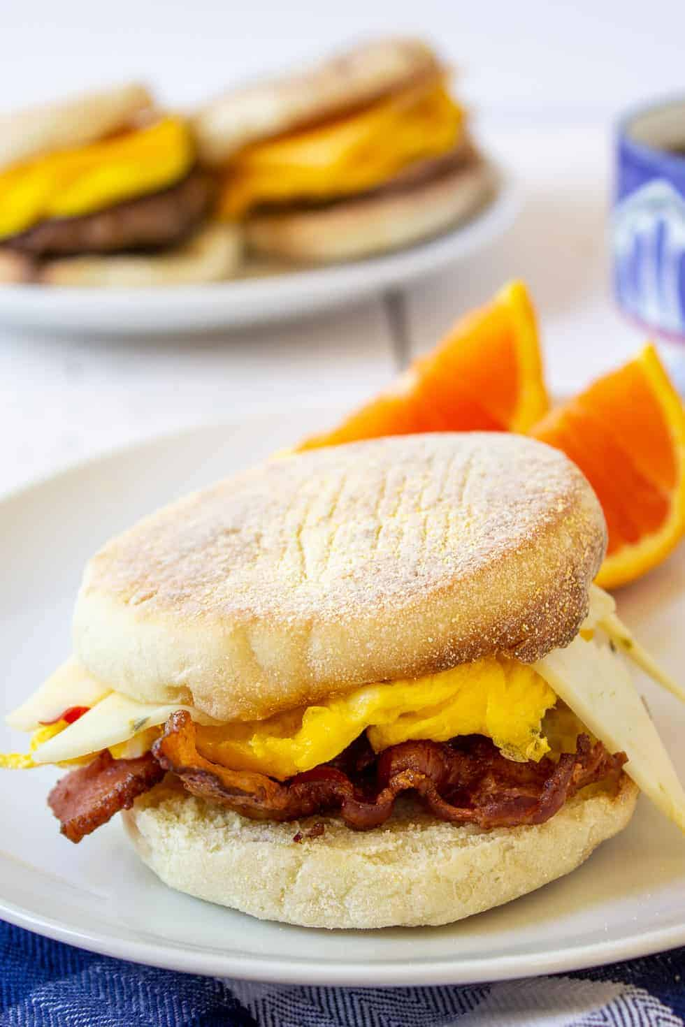 A sandwich made with English muffins, egg, bacon and cheese.