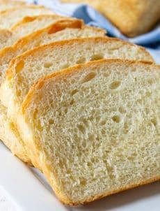 Slices of homemade white bread arranged on a white platter.