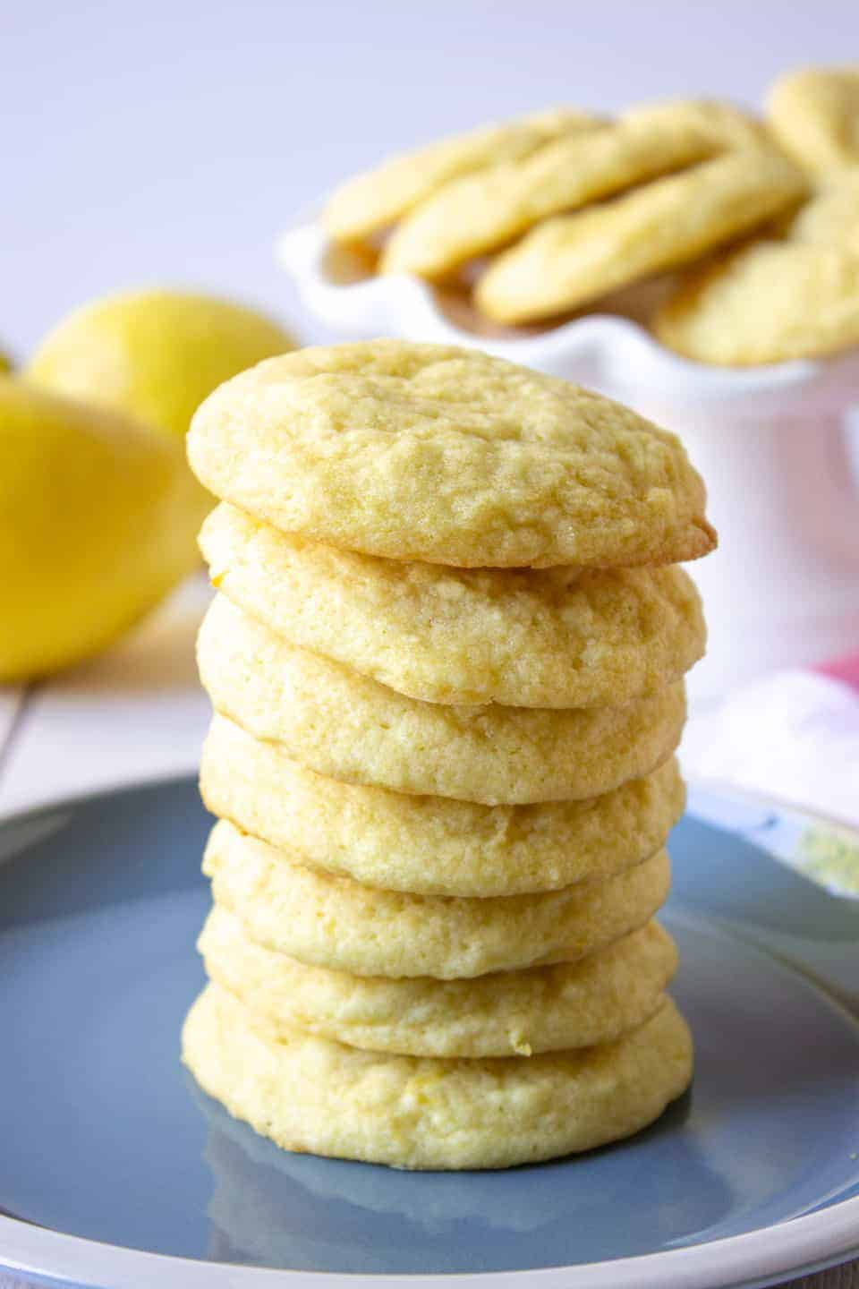 A tall stack of sugar cookies on a blue plate.