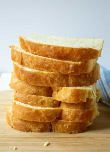 Sliced bread stacked on top of each other creating a tall tower of bread.