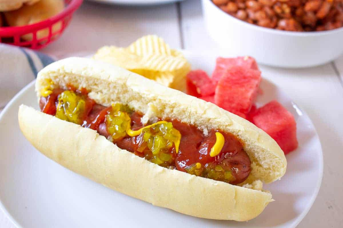 A hot dog topped with ketchup, mustard and relish sitting in a bun.