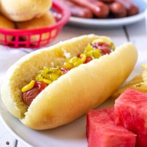 A hot dog bun with a hot dog topped with condiments.