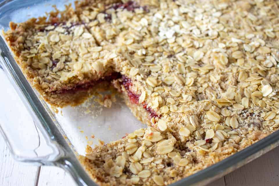 Raspberry bars in a pan with one slice removed.
