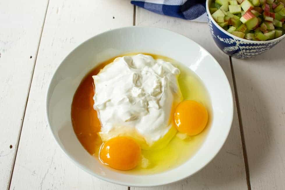 A bowl with sour cream, eggs, butter and vanilla.