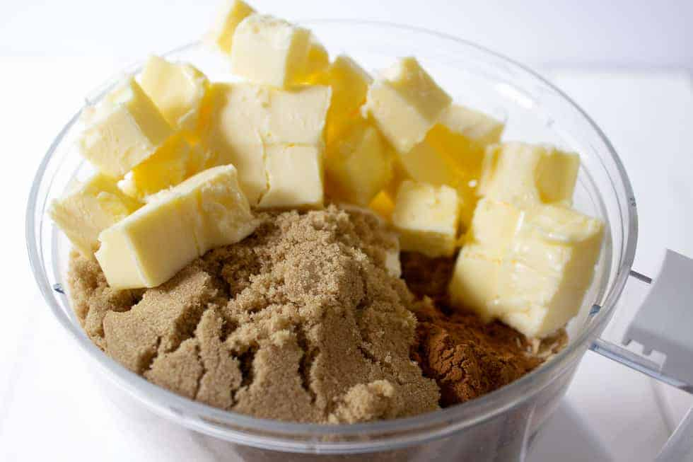 A food processor filled with butter and brown sugar.