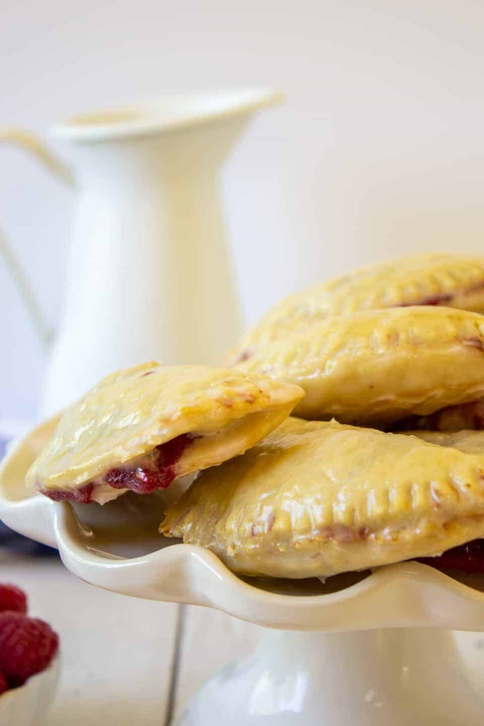 Hand pies stacked on a white cake plate.