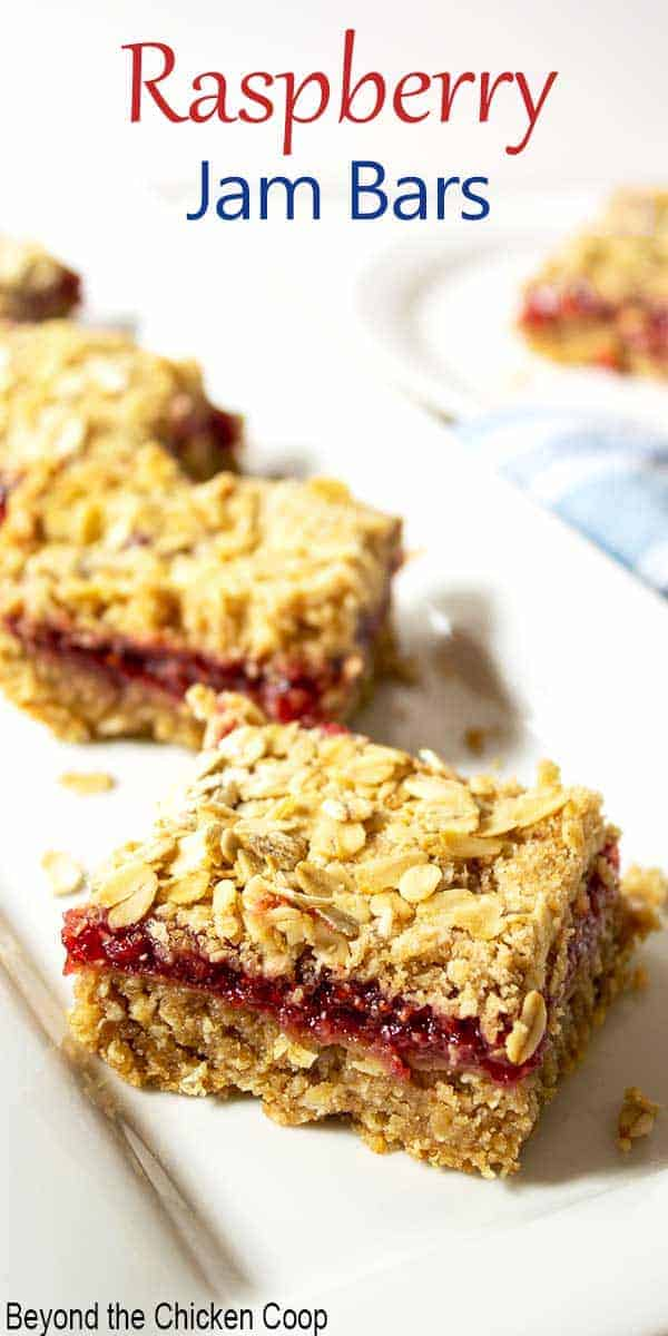 Oat bars filled with raspberry jam on a white platter.