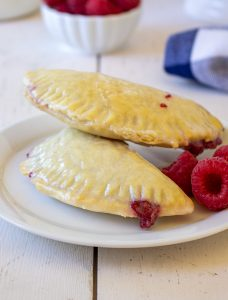Baked raspberry turnovers on a white plate with fresh raspberries.
