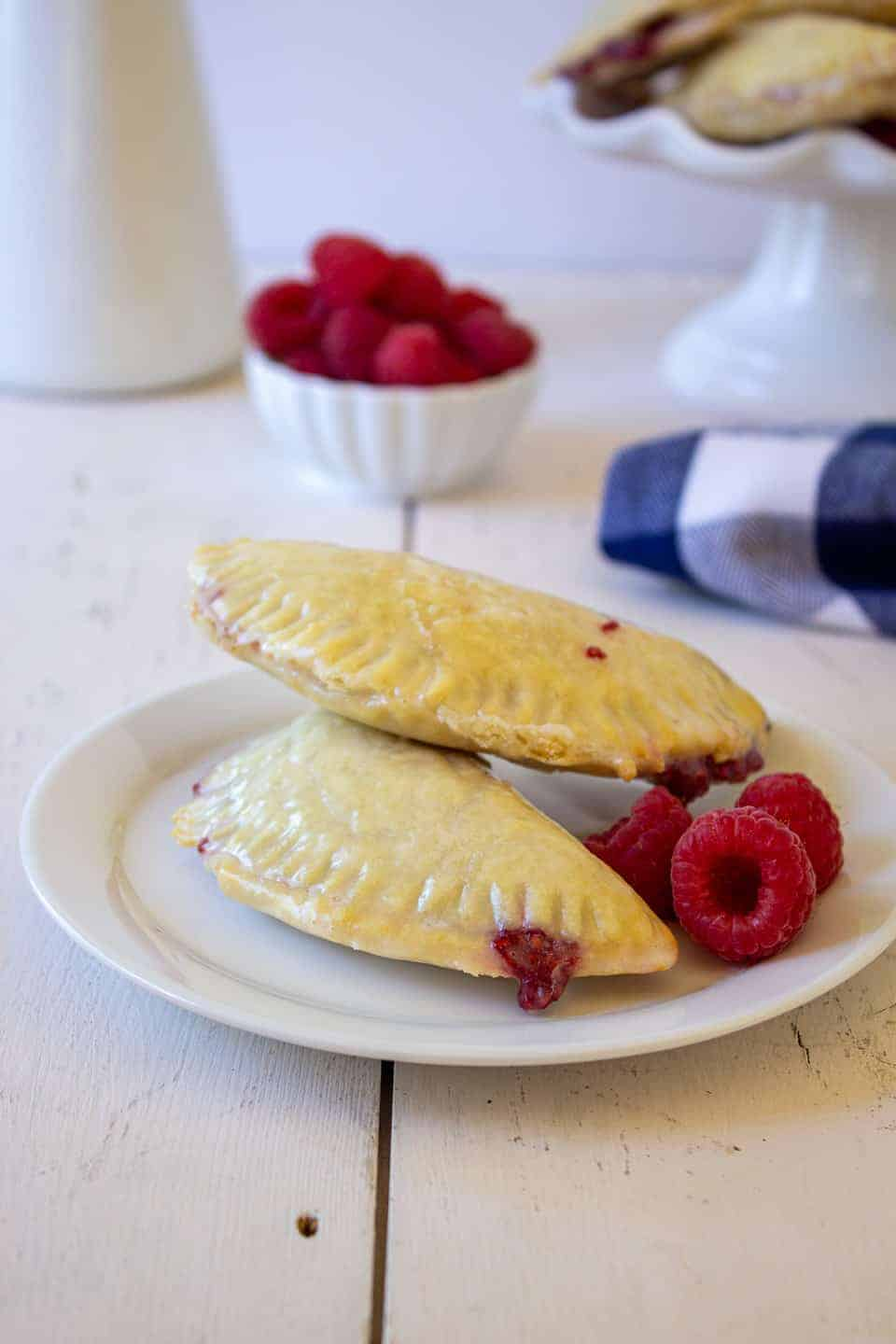Two Raspberry Hand Pies on a plate.