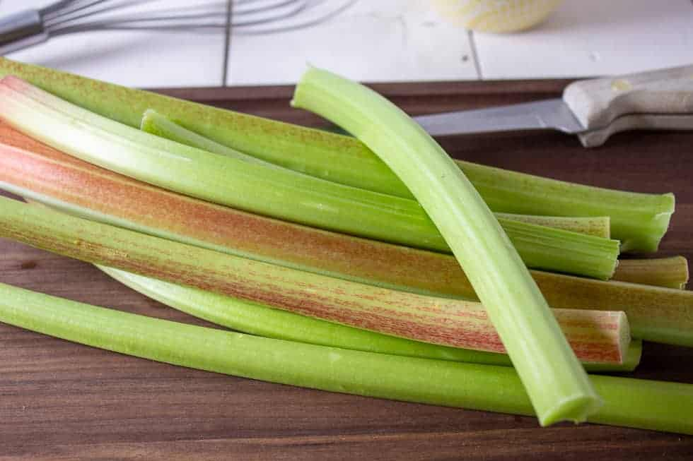 Stalks of rhubarb on a wooden cutting board.