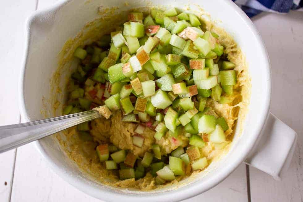 Chopped rhubarb being added to muffin batter.