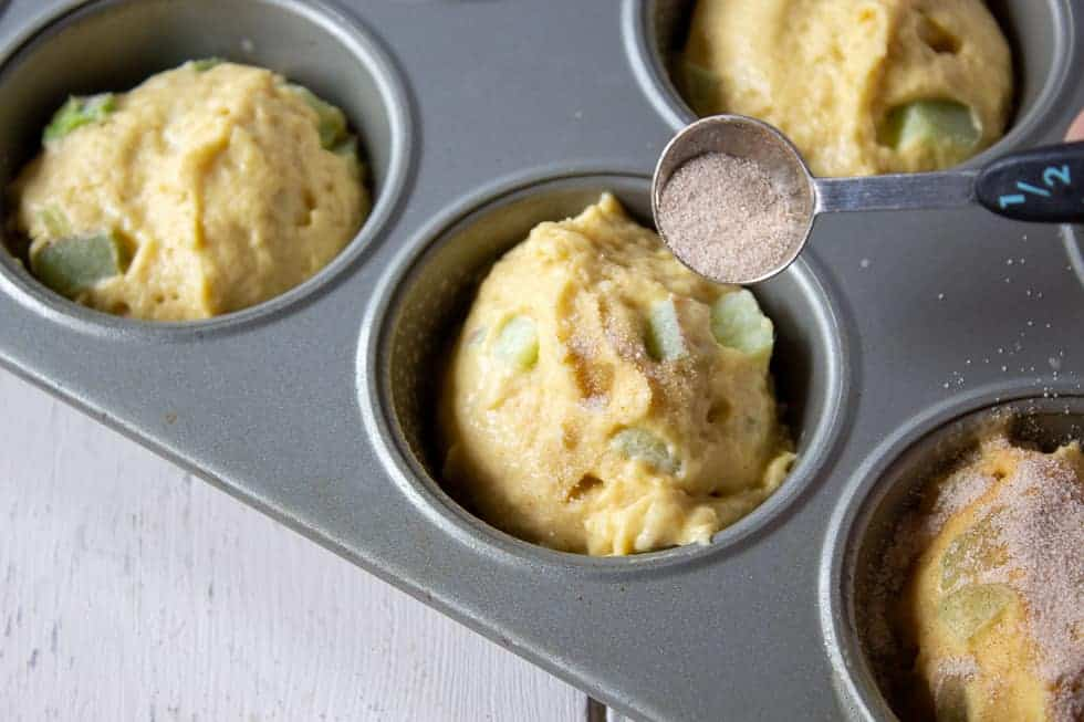 A muffin tin filled with rhubarb muffin batter being topped with cinnamon and sugar.