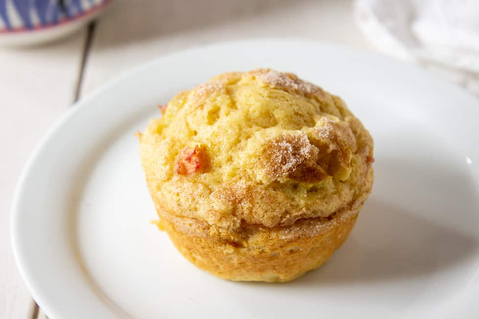 One rhubarb muffin on a small white plate.