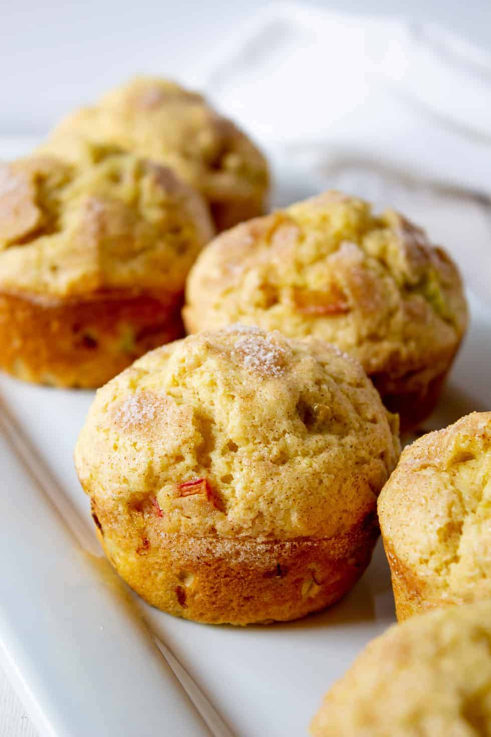 A white platter filled with fresh rhubarb muffins.