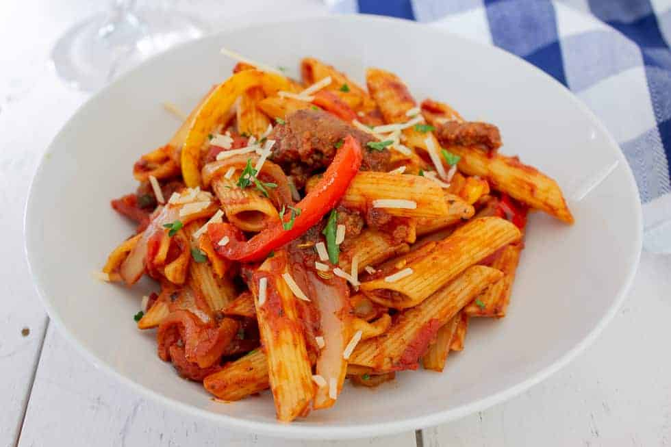 A white bowl filled with penne pasta, tomato sauce and peppers and onions.