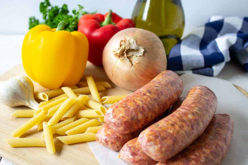 An arrangement of uncooked sausage, pasta and fresh onions and bell peppers on a wooden board.