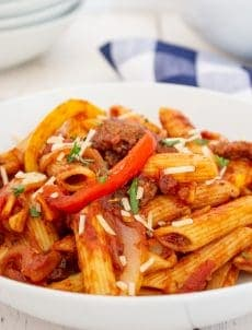 A white bowl filled with pasta with peppers and sausage.