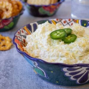 Artichoke dip topped with sliced jalapenos in a colorful bowl.