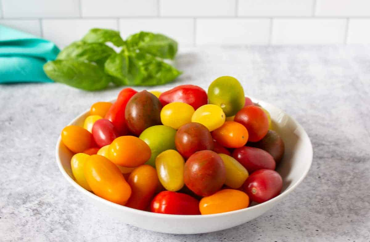 A bowl filled with green, yellow, red and orange cherry tomatoes.