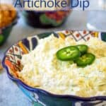 A colorful blue bowl filled with artichoke dip and topped with sliced jalapenos.