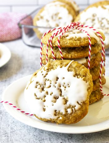A plate with a stack of iced oatmeal cookies with red and white twine.