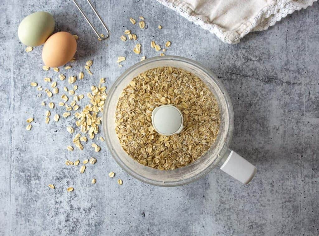 A food processor bowl filled with oats.