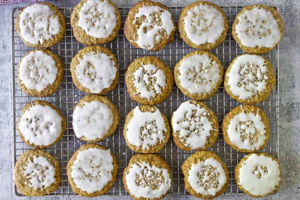 Rows of iced oatmeal cookies on a baking rack.