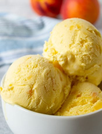 Scoops of peach ice cream in a small white bowl.