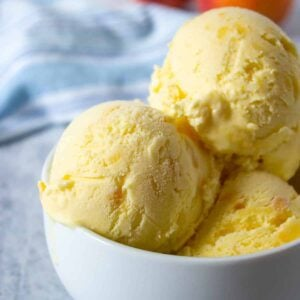 Scoops of peach ice cream in a white bowl.