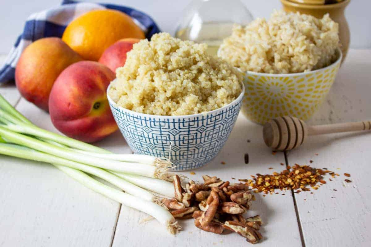Bowls of quinoa and rice with fresh peaches and green onions next to the bowls.