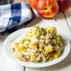 Quinoa, Rice and Peach Salad on a small white plate with fresh peaches in the background.