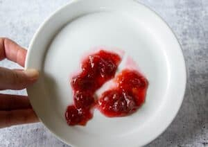Rhubarb jam being tested on a white plate.