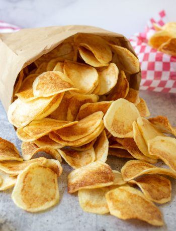 Homemade potato chips spilling out of a brown paper bag.