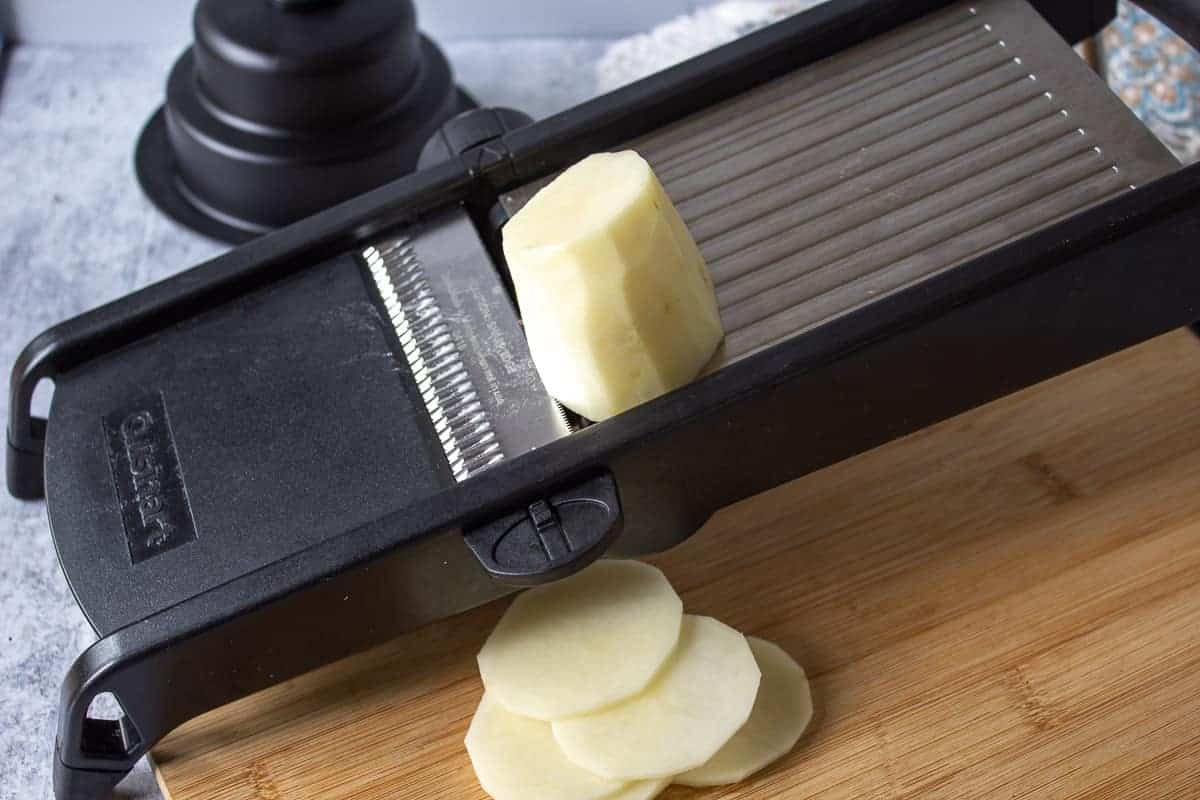 Potatoes being sliced on a mandoline.