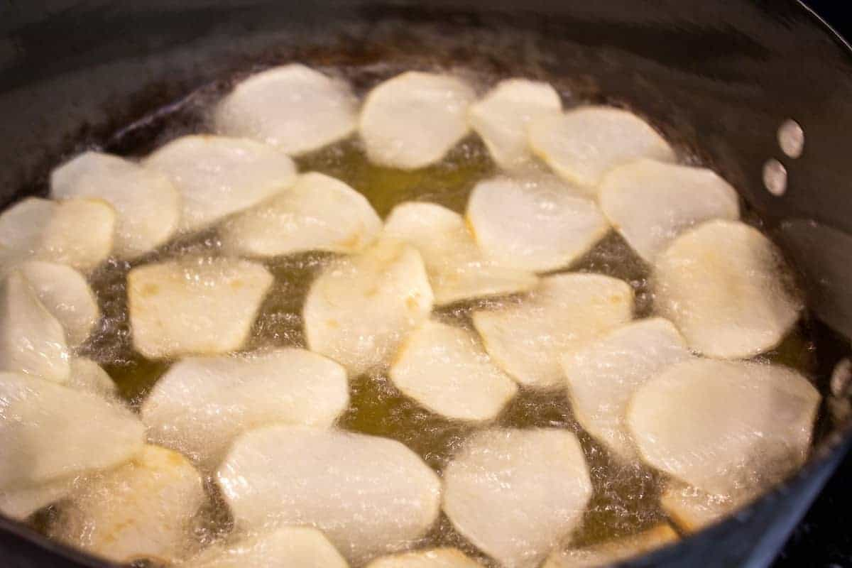 Potato chips frying in a pot of hot oil.