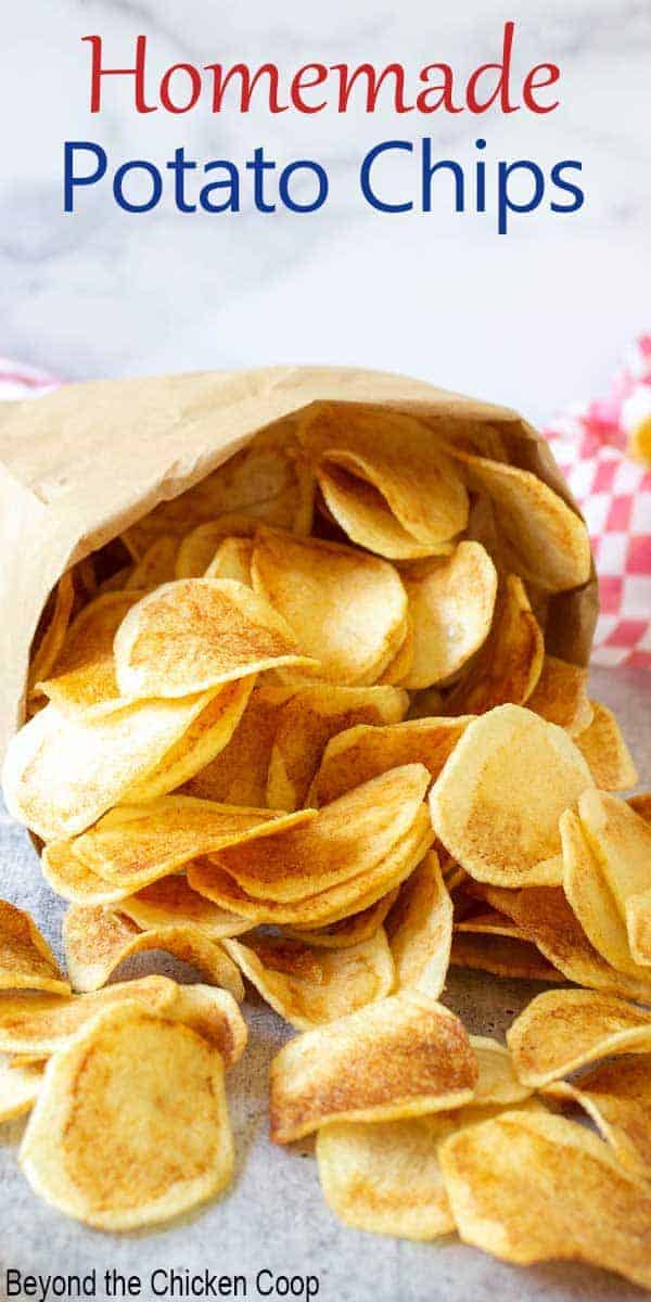 Golden potato chips spilling out of a brown paper bag.