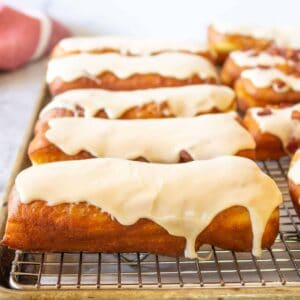 Frosted maple bars on a baking rack.