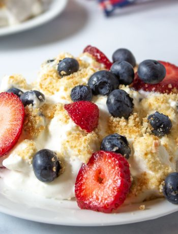 A plate full of whipped cream with fresh strawberries and blueberries.