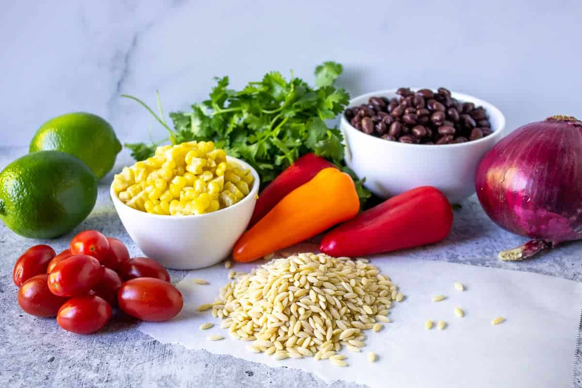 An arrangement of ingredients, including orzo, tomatoes, corn, black beans, bell peppers, cilantro and a red onion.