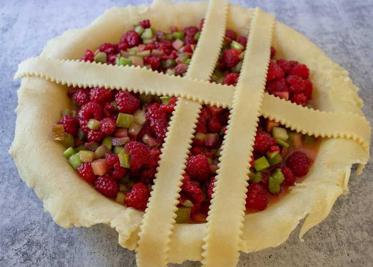 Building a top crust on a rhubarb pie with lattice strips.