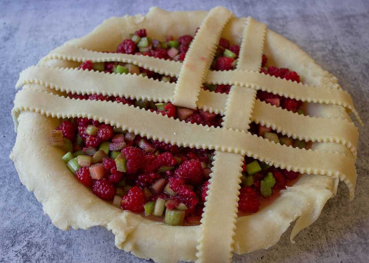 Folding back a lattice strip to create the pattern on top of a pie.