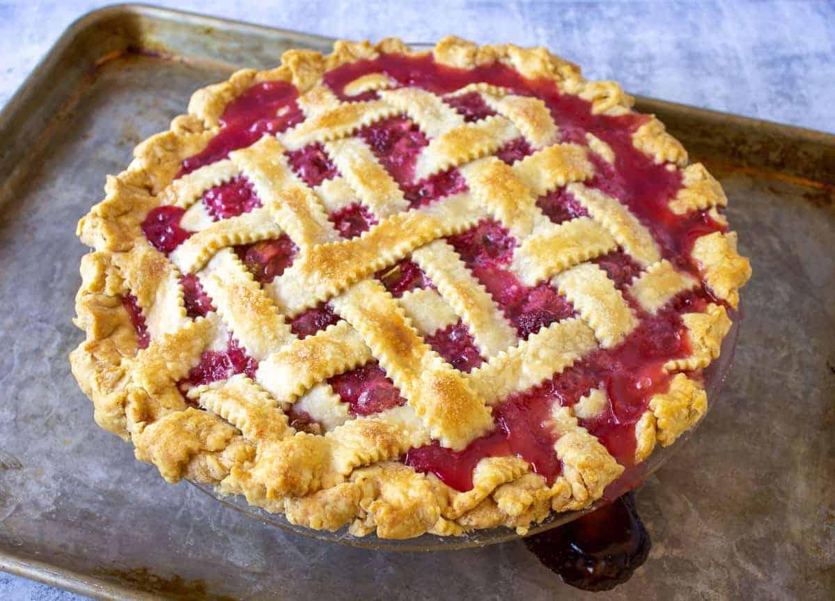 Raspberry Rhubarb Pie with a lattice crust on a baking sheet.