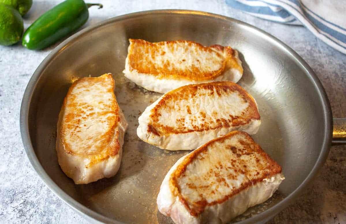 Seared pork chops in a pan.