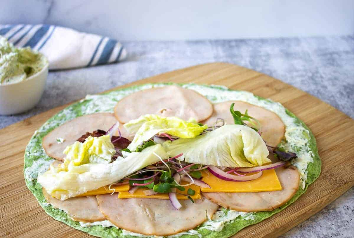 Lettuce added on top of a sandwich wrap.