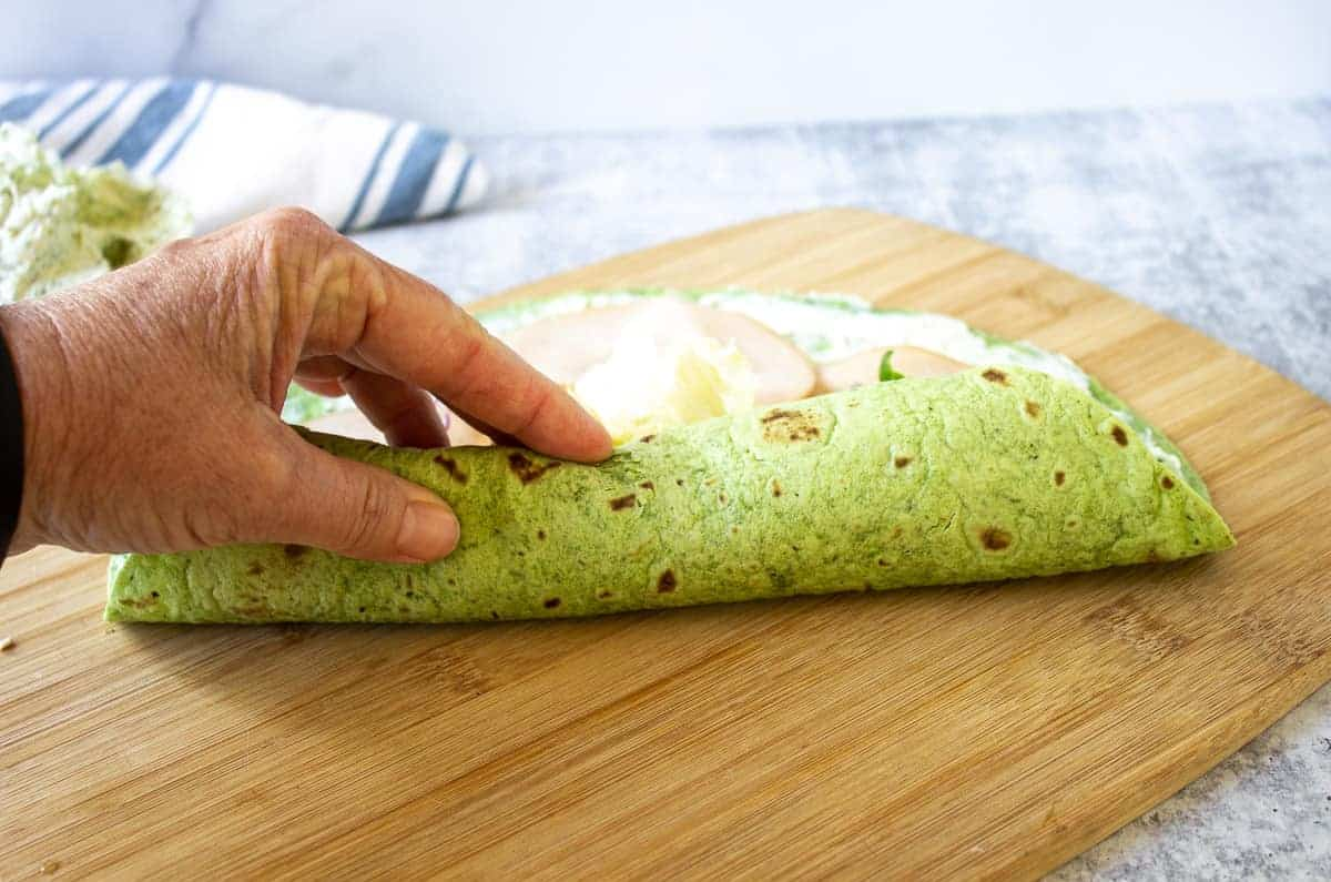 Rolling up a green tortilla wrap.