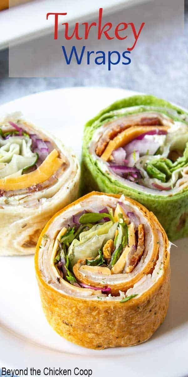 Three slices of turkey club wraps on a plate.
